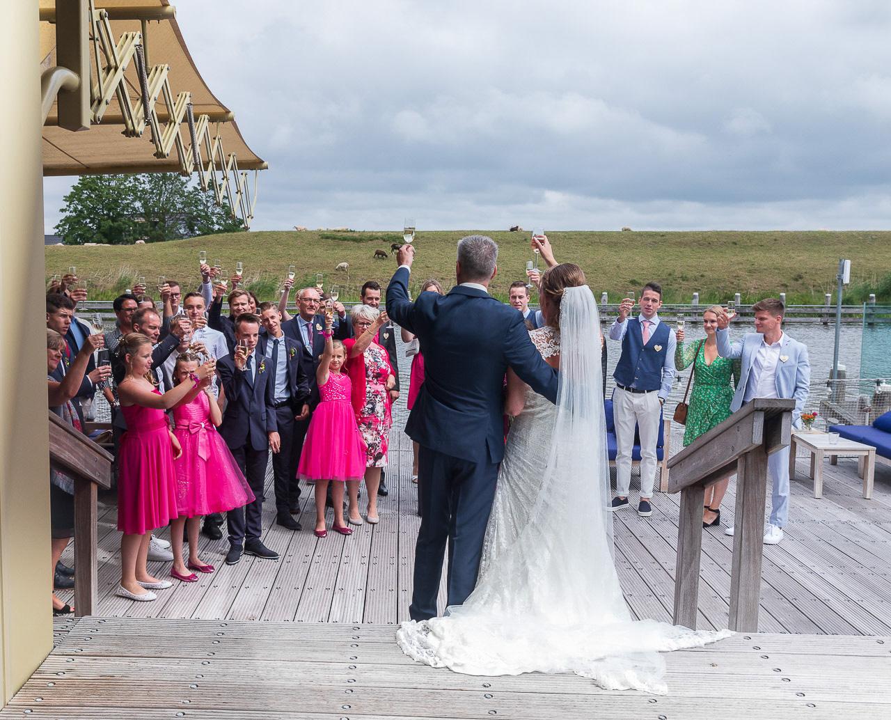 Bruidsfotografie; trouwfotograaf; Bruidspaar proost met alle gasten
