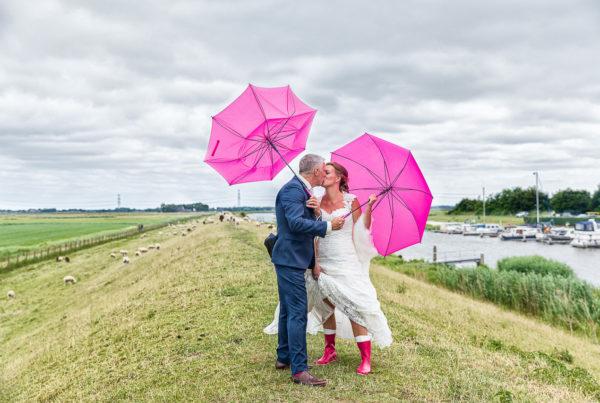 Bruidspaart poseert met roze paraplues en roze regenlaarzen op de dijk langs het Reitdiep, in Garnwerd.