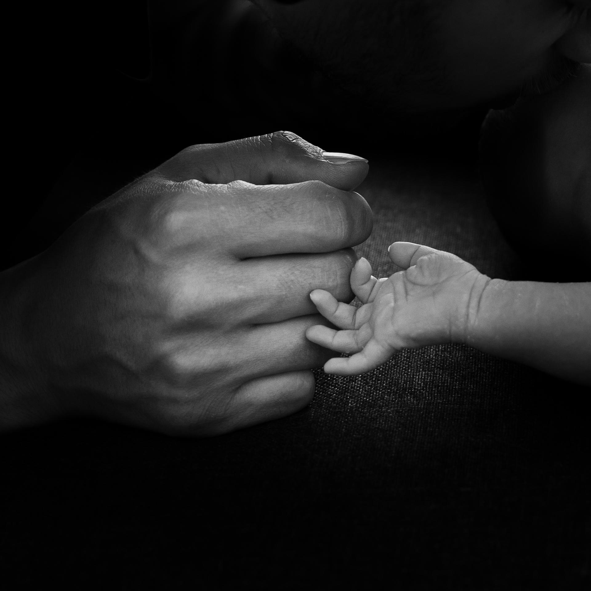 Handen van papa en pasgeboren zoon tegen elkaar