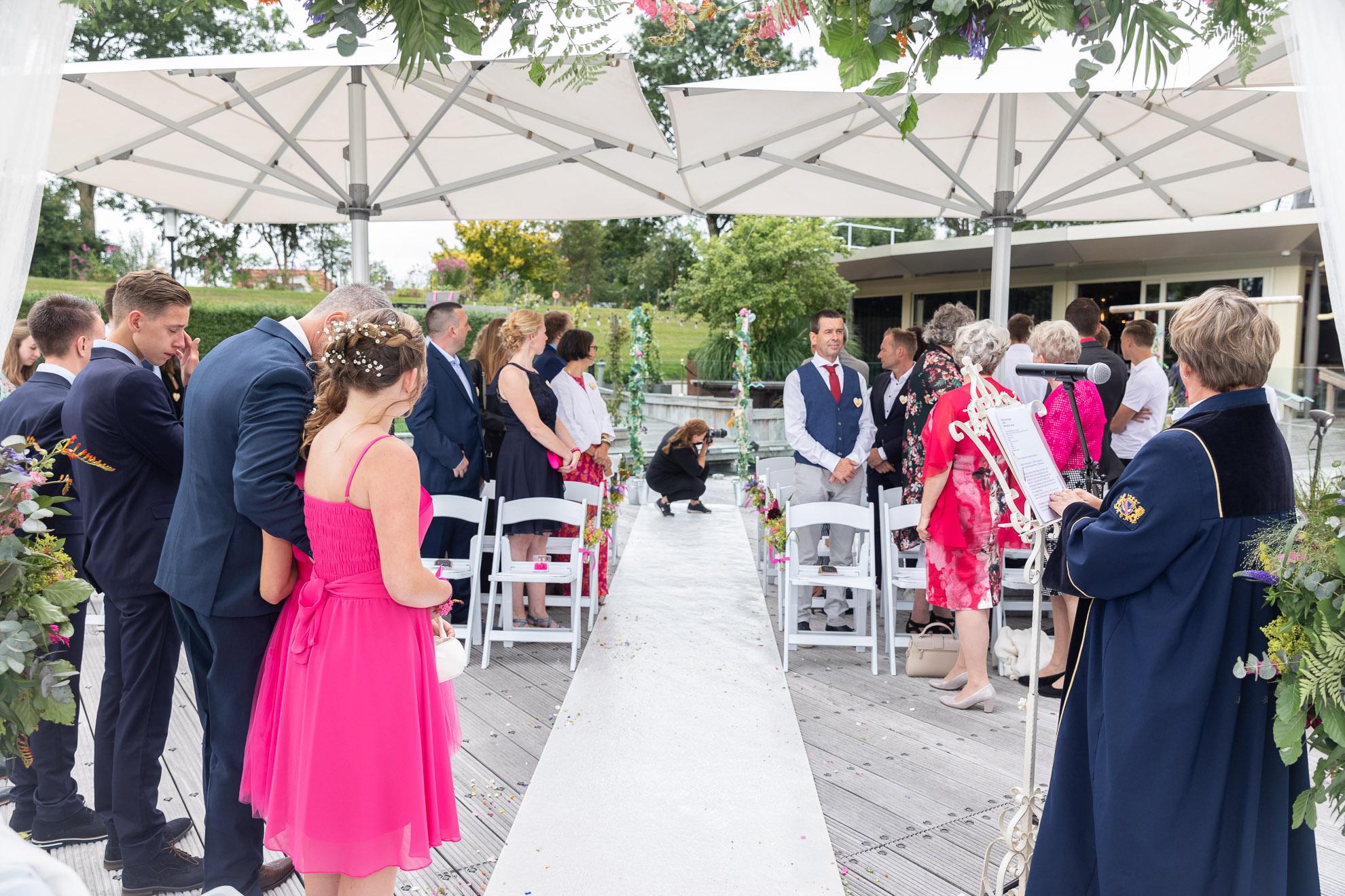 Second shooter fotografeert de bruid die in aantocht is.